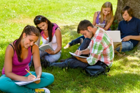 group study: Students sitting in park studying reading writing teens campus schoolyard