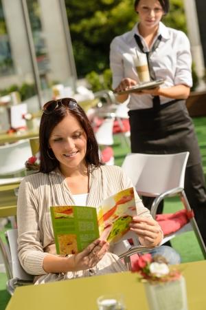 bringing: Woman checking menu waitress bringing order coffee cafe bar smiling