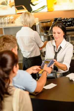 pay bills: Man paying bill at cafe using card bill happy waitress Stock Photo
