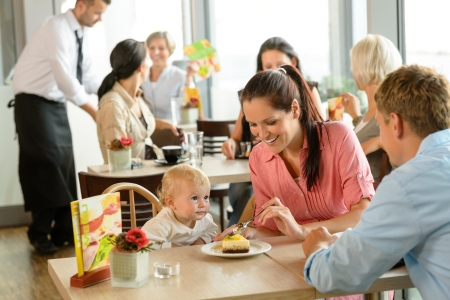 diner: Couple feeding their child cake at cafe restaurant woman man