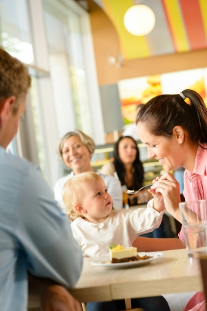 Father and mother feeding child cake cafe woman man eating Zdjęcie Seryjne