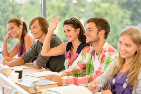 studious: High-school student raising her hand in class lesson teenagers study