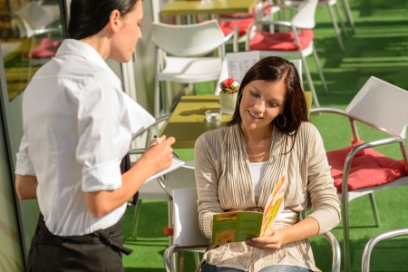 Woman deciding order from waitress at cafe terrace looking menu photo