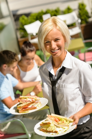 adult sandwich: Waitress bringing sandwiches on plates fresh lunch restaurant terrace