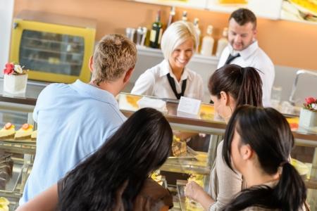 gl�cklicher kunde: Menschen kaufen Kuchen im Caf� bar Warteschlange Frauen zeigen Dessert Lizenzfreie Bilder