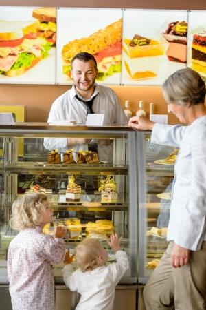 Grandchildren asking grandmother for cakes at cafe dessert appetite restaurant Stock Photo