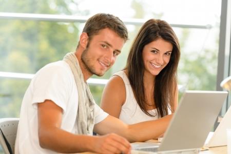 adolescentes estudiando: Alumnos de secundaria usando la computadora portátil para la escuela de biblioteca proyecto académico sonriente