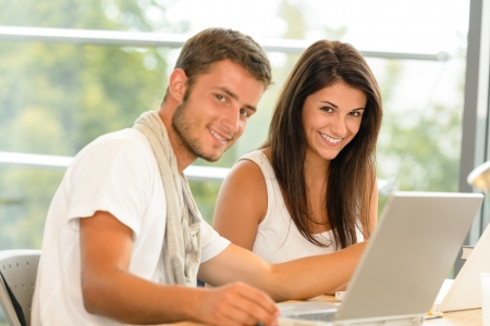 High-school pupils using laptop for school project academic library smiling Stock Photo - 15231179