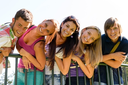 having a break: Teens having fun in park leaning fence happy students relaxing