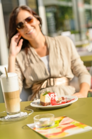 Cheesecake and latte at cafe terrace bar smiling woman sitting Stock Photo - 15236231