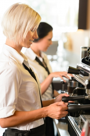 maker: Waitresses at work make coffee machine cafe smiling woman espresso Stock Photo