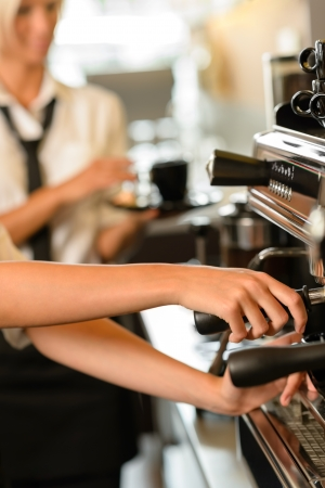 busy restaurant: Close up hands waitress make coffee at work espresso machine Stock Photo