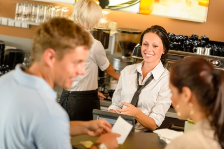 pay bills: Couple paying bill at cafe cash desk smiling waitress bar Stock Photo