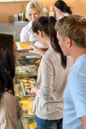 Customers waiting in line to buy dessert woman man cafe photo