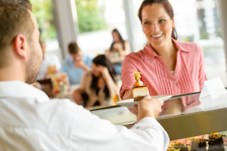 Waiter giving woman cake plate at cafe happy man service