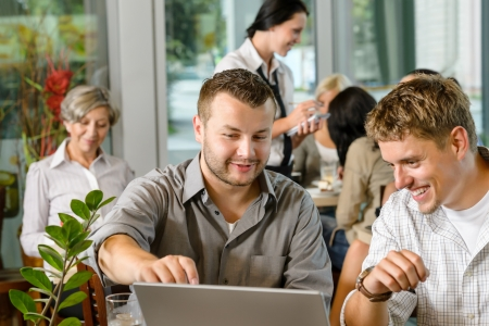 Men business partners working on laptop cafe restaurant photo