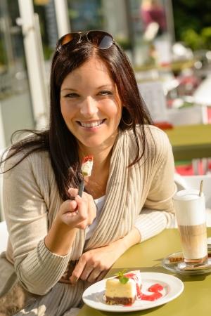 ätande: Kvinna äter cheesecake på café bar glada leende restaurang dessert