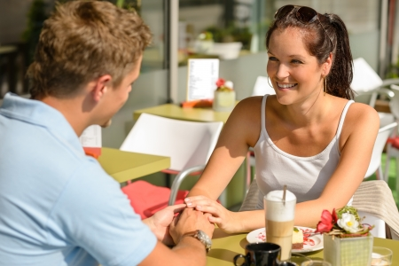Couple flirting holding hands at cafe bar restaurant terrace sunny Stock Photo