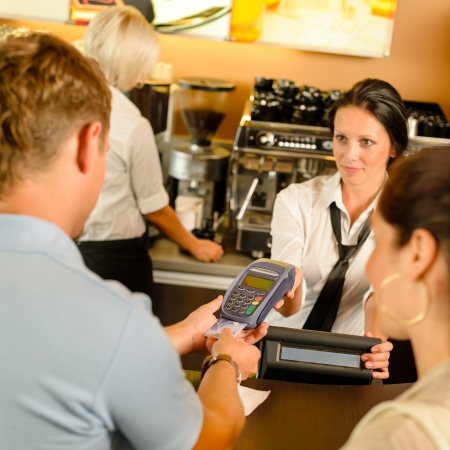 maquina registradora: Hombre que paga con tarjeta de cr�dito en cajero servicio de cafeter�a mujer Foto de archivo