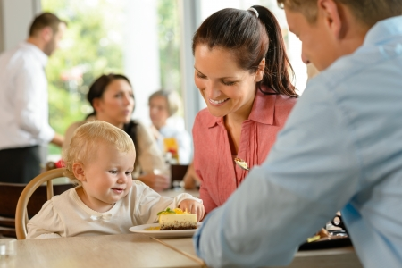 Mother and father with child eating cake woman man cafe photo