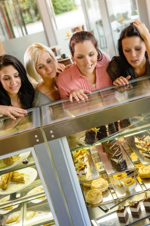 Women friends looking at cakes in cafe craving window display photo