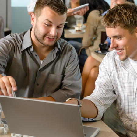 business help: Men business partners working on laptop cafe restaurant Stock Photo