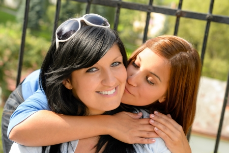Daughter kissing her mother outdoors teen happy loving together leisure photo