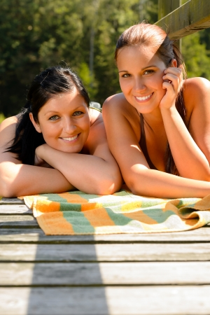 Mother and daughter sunbathing on pier smiling teen relaxing vacation photo