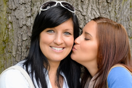 Daughter giving her mother a kiss outdoors teen happy bonding photo