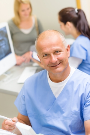 dental clinic: Professional dental surgeon sitting in office with assistant nurse