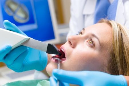 laboratorio dental: Mujer con la boca abierta y herramientas dentales tienen chequeo dientes