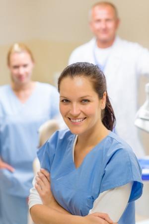 laboratorio dental: Mujer sonriente higienista dental con el equipo de profesionales médicos estomatología