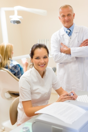uniformes de oficina: Dentista con asistente sonriente en estomatología atención de la salud profesional de la oficina Foto de archivo