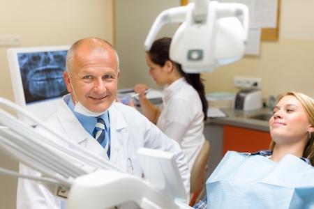 laboratorio dental: Dentista amistoso femenino con la visita periódica del paciente en cirugía dental Foto de archivo