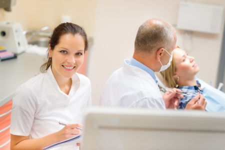 Smiling dental nurse prepare patient documentation stomatology clinic photo