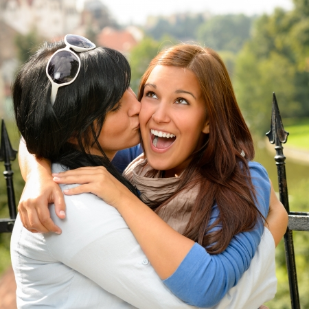Mother kissing her daughter happy embrace outdoors teen leisure loving photo
