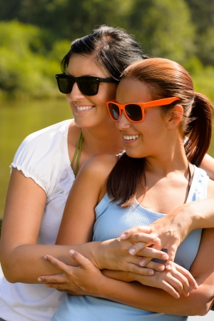 coziness: Mother and daughter relaxing in park smiling teen summer affectionate