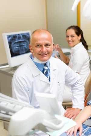 x ray equipment: Professional dental surgeon sitting in office with assistant nurse