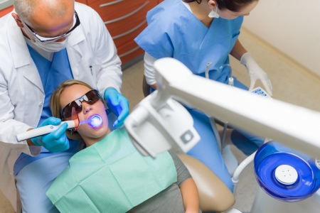 protective glasses: Young woman patient have dental surgery dentist use UV lamp Stock Photo