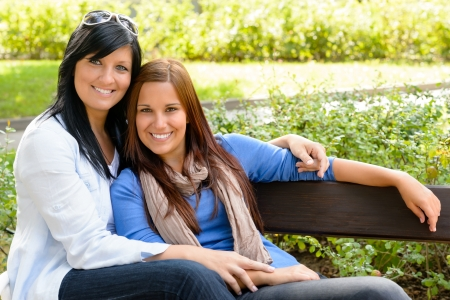 mother on bench: Mother and daughter relaxing on park bench happy bonding teen