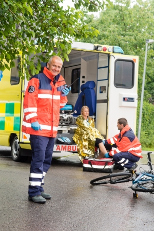 accident at work: Emergency radio calling paramedics helping woman bike accident ambulance