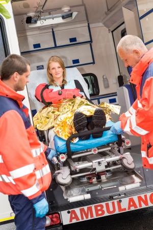 Paramedics with injured woman on stretcher in ambulance helping accident photo