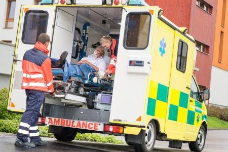скорая помощь: Медработники положить больного человека кислородную маску в машине скорой помощи