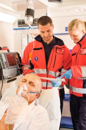 Paramedici lezen EKG in de ambulance de patiënt hulp noodsituatie vrouw man