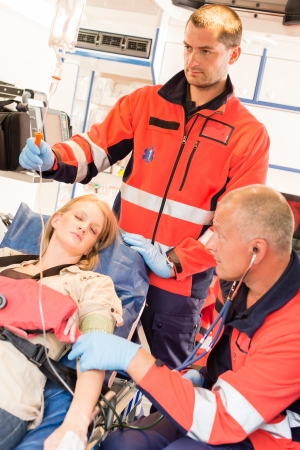 Unconscious patient woman emergency ambulance paramedics measuring blood pressure Stock Photo - 15335909