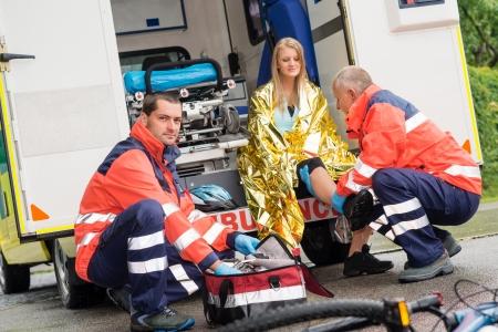 Bike accident woman emergency doctor checking leg in ambulance