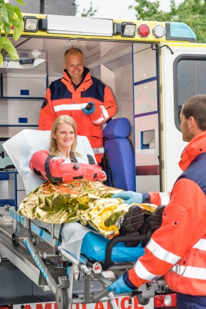 broken arm: Paramedics helping woman on stretcher in ambulance smiling accident victim