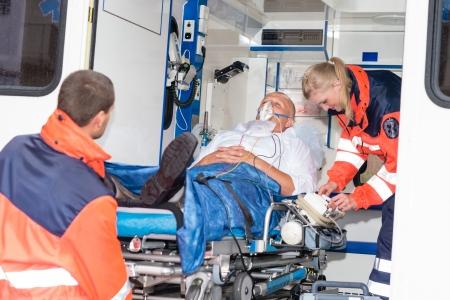 Paramedici zetten geduldig man zuurstofmasker in ambulance auto