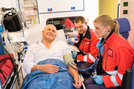 paramedic: Paramédicos de comprobación del pulso del paciente en ambulancia de emergencia gráfico coche médico Foto de archivo