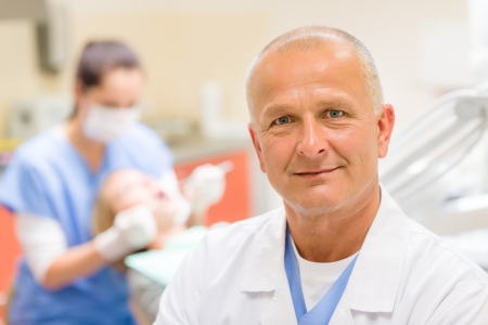 Portrait of mature dentist surgeon posing at office Stock Photo